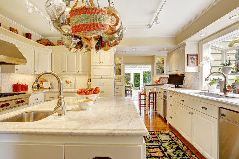 White kitchen with white granite tops, island and hanging pot rack